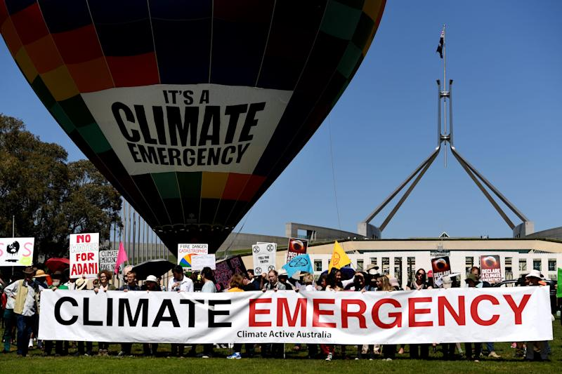 A hot air balloon with 'Climate Emergency' on it is seen in front of Parliament House on October 15, 2019, in Canberra, Australia. Protesters are demanding politicians declare a climate emergency.