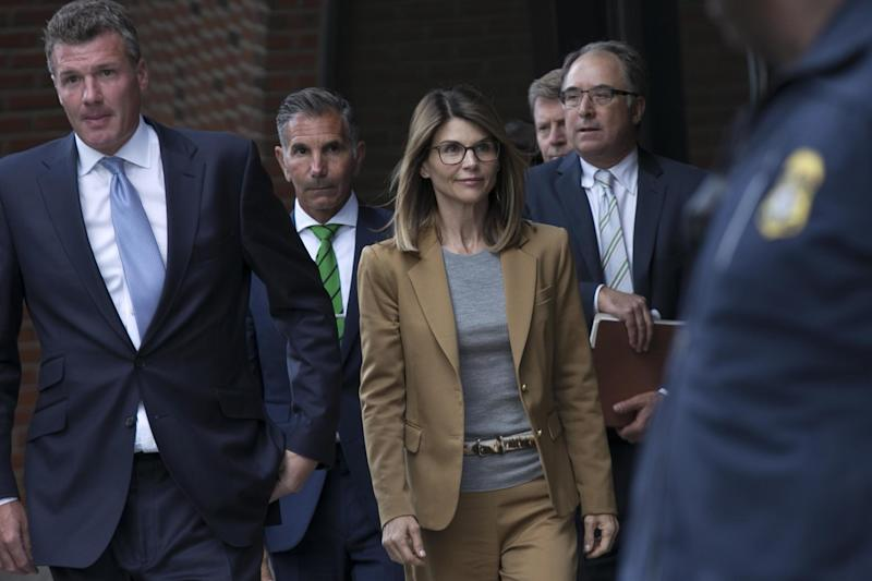 Lori Loughlin (center) and her husband Mossimo Giannulli (second left) leave court (EPA)