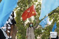 A woman with a partly destroyed Chinese flag stand between demonstrators with Uyghur flags as she attends a protest during the visit of Chinese Foreign Minister Wang Yi in Berlin, Germany, Tuesday, Sept. 1, 2020. German Foreign Minister Heiko Maas meets his Chinese counterpart at the foreign ministry guest house Villa Borsig for bilateral talks. (AP Photo/Markus Schreiber)