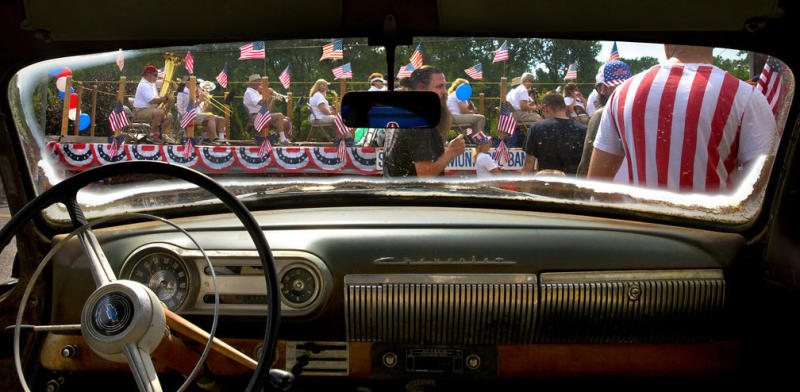 Members of the St. Charles Municipal Band roll past a 1953 Chevy on the lot of McNeil Motor Cars as the St. Charles Jaycees Riverfest Parade makes its way through the Frenchtown neighborhood on Tuesday, July 4. (Photo by Robert Cohen/St. Louis Post-Dispatch)