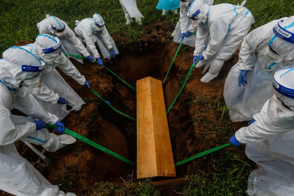 Volunteers lower the body of a Covid-19 victim in the grave for burial at Bagan Ajam Muslim Cemetery, August 24, 2021. — Picture by Sayuti Zainudin