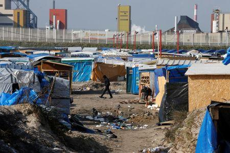 """A migrant walks past makeshift shelters in the northern area on the final day of the dismantlement of the southern part of the camp called the 'Jungle"""" in Calais"""