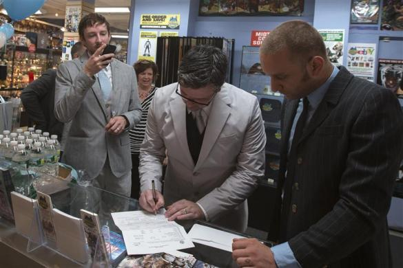 Jason Welker (L) photographs his partner Scott Everhart as he signs their marriage license after their wedding ceremony at a comic book retail shop in Manhattan, New York June 20, 2012.