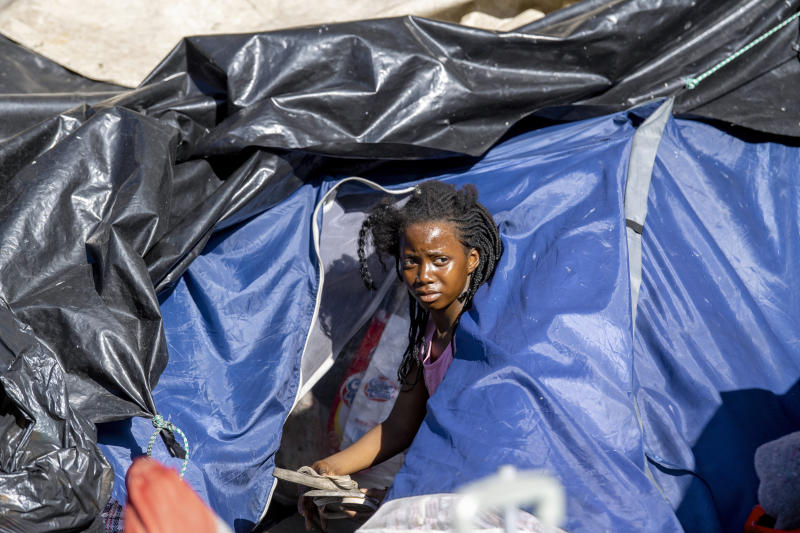 A young girl gathers her belongings outside the Central Methodist Mission Church in Cape Town, South Africa, Sunday, March 1, 2020 as city officials and police move in to evict people. Hundreds of migrants have been removed from central Cape Town by South African authorities following a months-long stand-off. The migrants removed on Sunday had demanded to be relocated to other countries claiming they had been threatened by xenophobic violence last year.  (AP Photo)