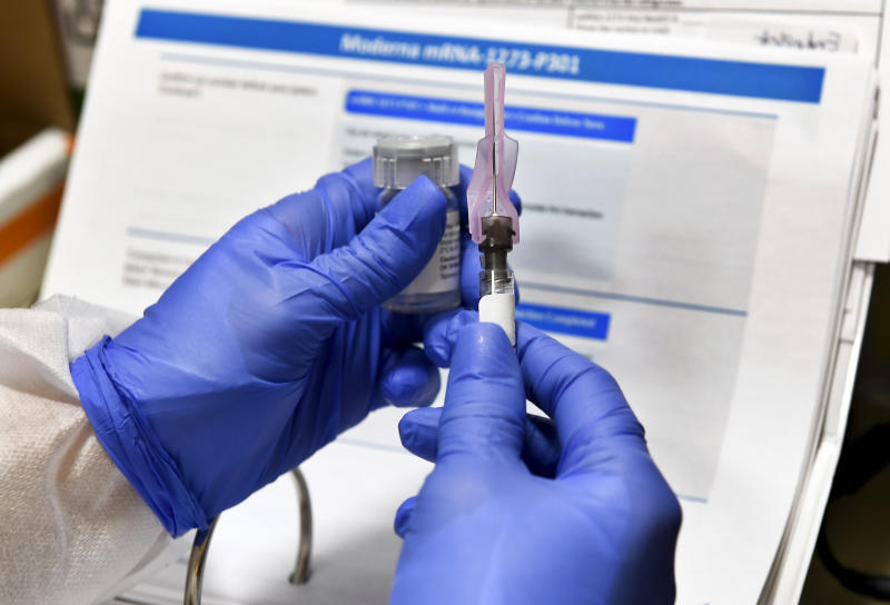 Nurse Kathe Olmstead prepares a shot as the world's biggest study of a possible COVID-19 vaccine, developed by the National Institutes of Health and Moderna Inc., gets underway Monday, July 27, 2020, in Binghamton, N.Y. (AP Photo/Hans Pennink)