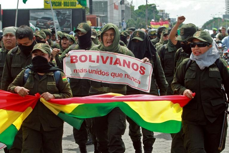 Police officers in Santa Cruz, Bolivia, have joined anti-government protests; they are seen marching on November 9, 2019, carrying a banner that reads 'Bolivians more united than ever' (AFP Photo/DANIEL WALKER)