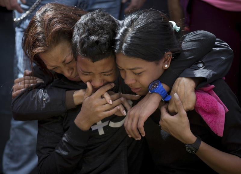 The relatives of Jose Diaz Pimentel, mother Rosa Pimentel, right, and his son Yandribell Diaz and another person, cry during Jose Diaz Pimentel's funeral service at a cemetery in Caracas Venezuela, Saturday, Jan. 20, 2018. Jose Diaz Pimentel and Abraham Agostini, members of the rebel group led by Venezuelan former police Oscar Perez, who died at the beginning of the week in an operation of the security forces, were buried in a controlled manner by the authorities and between protests of their Relatives, who were prevented from accessing the cemetery. (AP Photo/Fernando Llano)