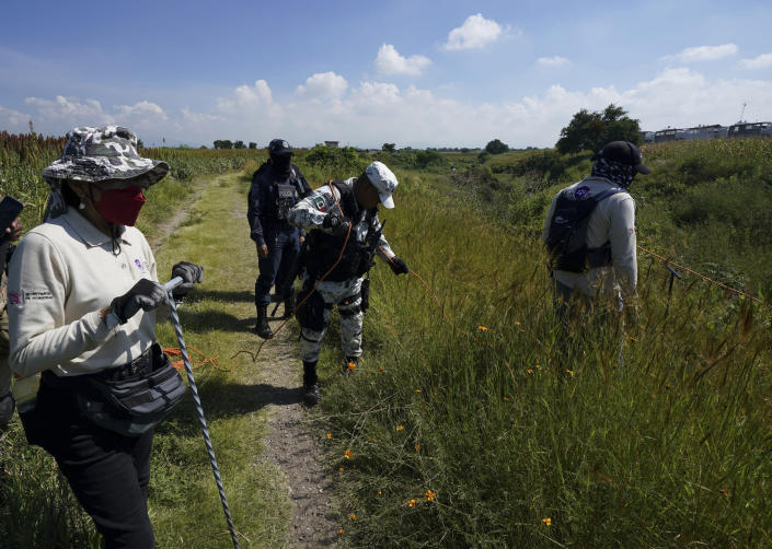 National Guards and volunteers search for disappeared persons on the outskirts of Cuautla, Mexico, Tuesday, Oct. 12, 2021. The government's registry of Mexico's missing has grown more than 20% in the past year and now approaches 100,000. (AP Photo/Fernando Llano)
