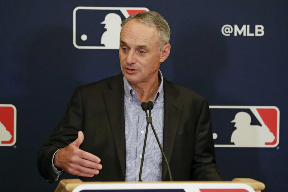 Rob Manfred in a black suit jacket, striped collared shirt, in front of an MLB backdrop.