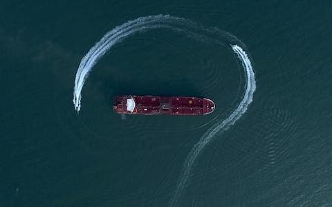 A speedboat of Iran's Revolutionary Guard is photographed moving around the British-flagged oil tanker Stena Impero in the Strait of Hormuz - Credit: Morteza Akhoondi/Tasnim News Agency via AP