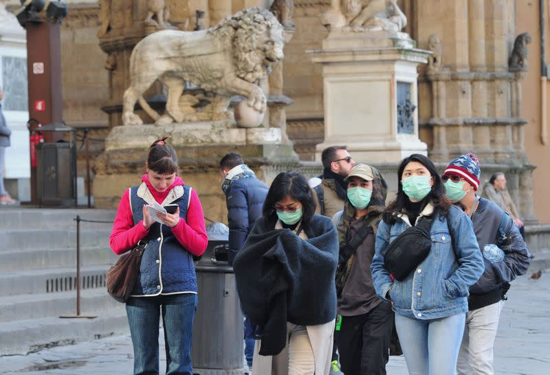 People wearing protective masks walk through Florence as Italy battles a coronavirus outbreak