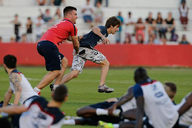 Cyril Praud, physical therapist for French team, runs after a soccer fan storming the pitch at the end of a training session at the Santa Cruz Stadium, in Ribeirao Preto, Brazil, Friday, June 13, 2014. France will play in group E of the 2014 Brazil soccer World Cup. (AP Photo/David Vincent)