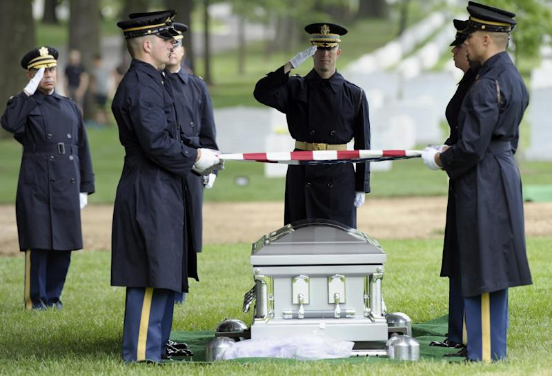 An American flag is held over the casket for Army Spc. 5 John L. Burgess, of Sutton Bay, Mich., who was the crew chief of a UH-1H Iroquois helicopter that crashed in 1970 in Binh Phuoc Province, South Vietnam, Tuesday, July 2, 2013, during funeral services at Arlington National Cemetery in Arlington, Va. Burgess is buried with those who were also killed in the crash, 1st Lt. Leslie F. Douglas Jr., of Verona, Miss.; lst Lt. Richard Dyer, of Central Falls, R.I.; and Sgt. 1st Class Juan Colon-Diaz, of Comerio, Puerto Rico. The Pentagon says remains representing Burgess, Dyer and Colon-Diaz will be buried as a group in a single casket. (AP Photo/Susan Walsh)