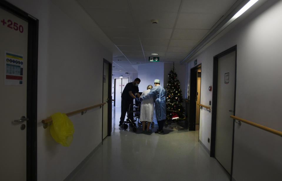 Two Belgian Army medics help a patient to walk who is recovering from COVID-19 at the St. Michiel Hospital in Brussels, Tuesday, Nov. 24, 2020. The Belgian military has been called into several hospitals and care homes to alleviate the stress on healthcare personnel. (AP Photo/Virginia Mayo)
