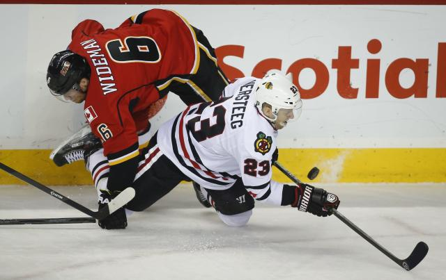 Chicago Blackhawks' Kris Versteeg, right, escapes a check from Calgary Flames' Dennis Wideman during the second period of an NHL hockey game in Calgary, Alberta, Wednesday, Nov. 27, 2013. (AP Photo/The Canadian Press, Jeff McIntosh)