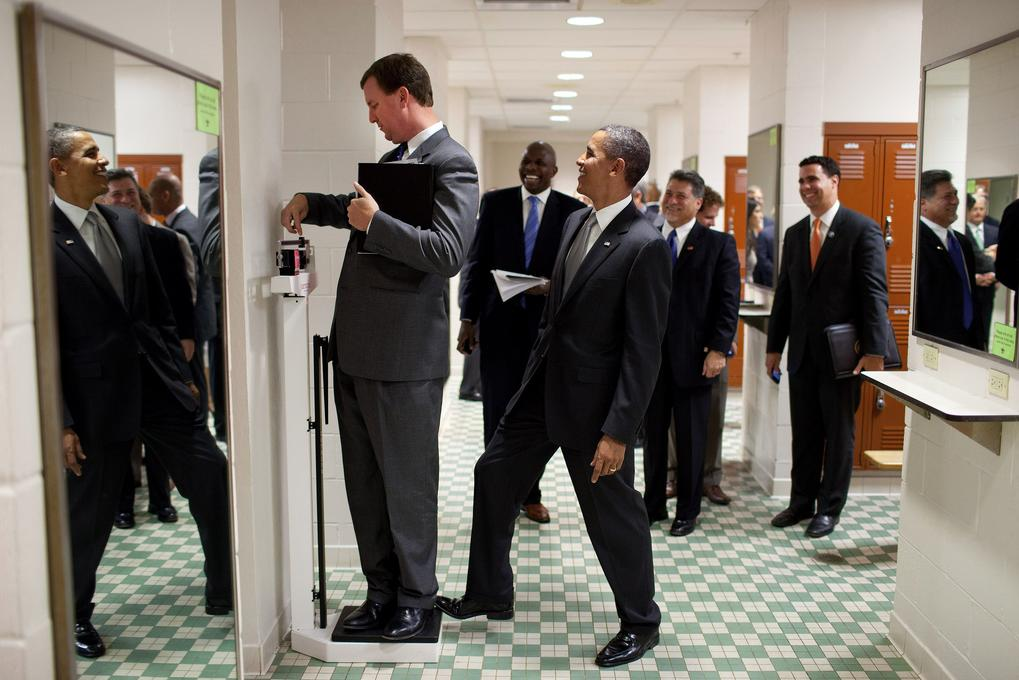 President Barack Obama jokingly puts his toe on the scale as Trip Director Marvin Nicholson, unaware to the President's action, weighs himself as the presidential entourage passed through the volleyball locker room at the University of Texas in Austin, Texas, Aug. 9, 2010. (Pete Souza/The White House)