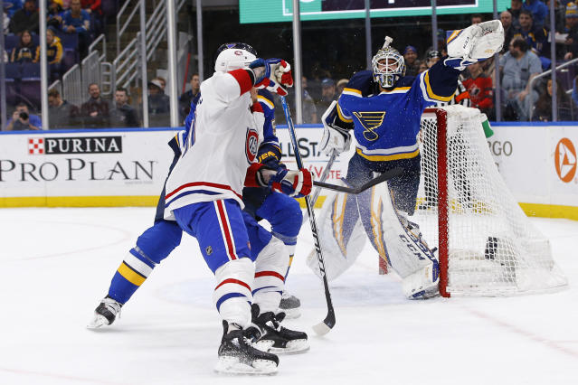 St. Louis Blues goaltender Jordan Binnington reaches for the puck after it was deflected by Montreal Canadiens' Nicolas Deslauriers, front, and Blues defenseman Colton Parayko, back, during the first period of an NHL hockey game Thursday, Jan. 10, 2019, in St. Louis. (AP Photo/Billy Hurst)