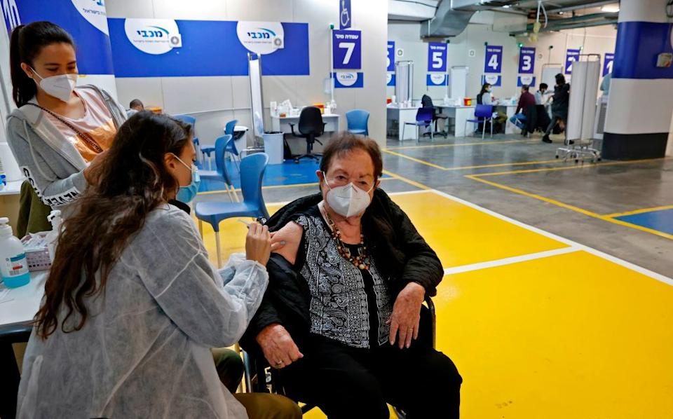 An elderly women gets vaccinated in the parking lot of a mall in Israel, where a mass hub was set up in January. Source: Getty