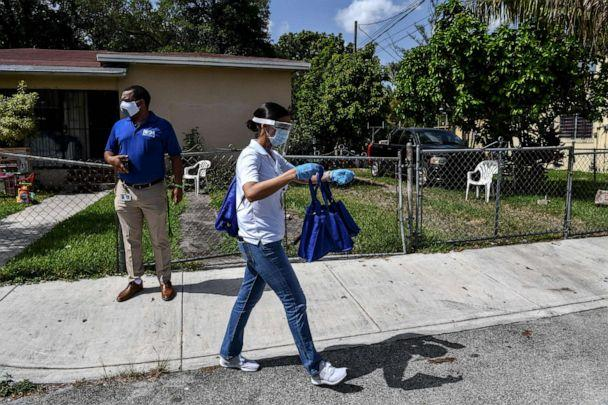 PHOTO: Catherimarty Burgos, a member of Miami-Dade County 'surge teams' distributes bags with masks, sanitizers, and gloves to educate people on how to stay safe from COVID-19, in a neighborhood of Miami, on June 30, 2020. (Chandan Khanna/AFP via Getty Images)