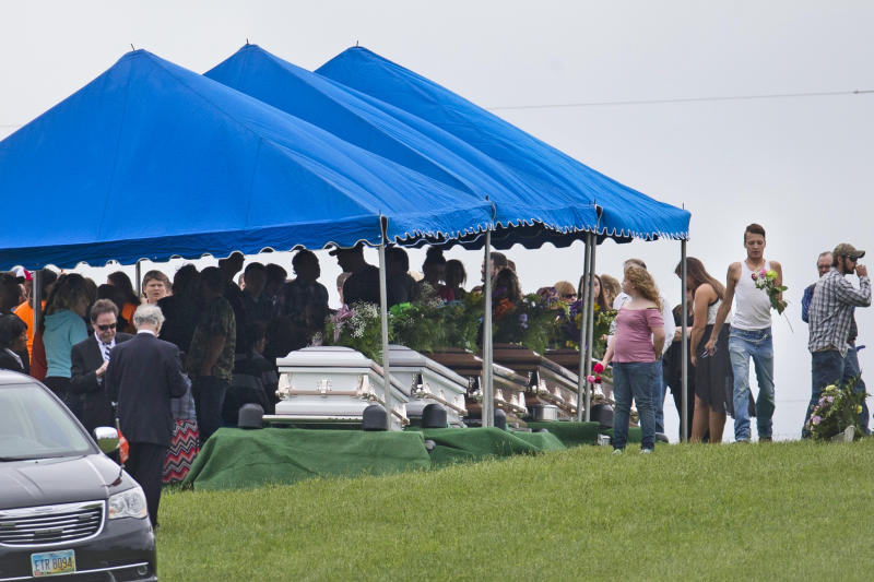 FILE – In this May 3, 2016, file photo, mourners gather around caskets for six of the eight members of the Rhoden family found shot April 22, 2016, at four properties near Piketon, Ohio, during funeral services at Scioto Burial Park in McDermott, Ohio. Ohio State Attorney General Mike DeWine and Pike County Sheriff Charles Reader planned a news conference Thursday, April 13, 2017, about the unsolved killings, as the anniversary of the massacre approaches. (AP Photo/John Minchillo, File)