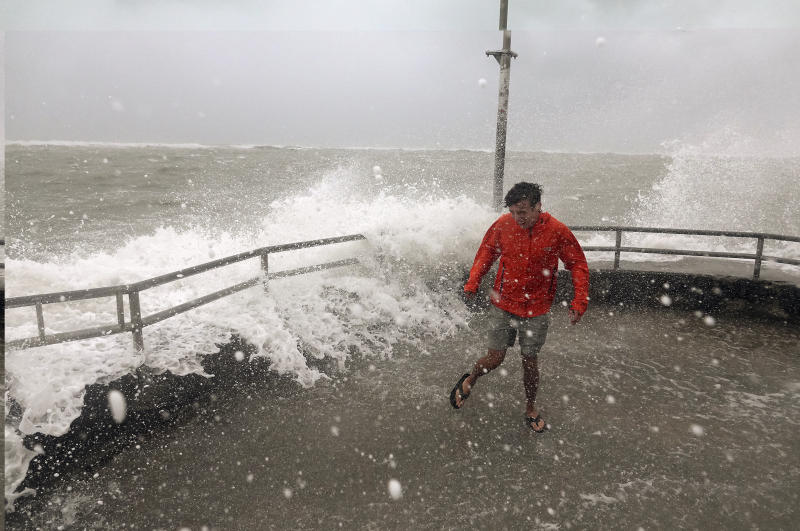 Brandon Ennis runs away from waves caused by Hurricane Dorian crashing over the jetty of the Jupiter inlet, Tuesday, Sept. 3, 2019, in Jupiter, Fla. (Photo: Joe Cavaretta/South Florida Sun-Sentinel via AP)