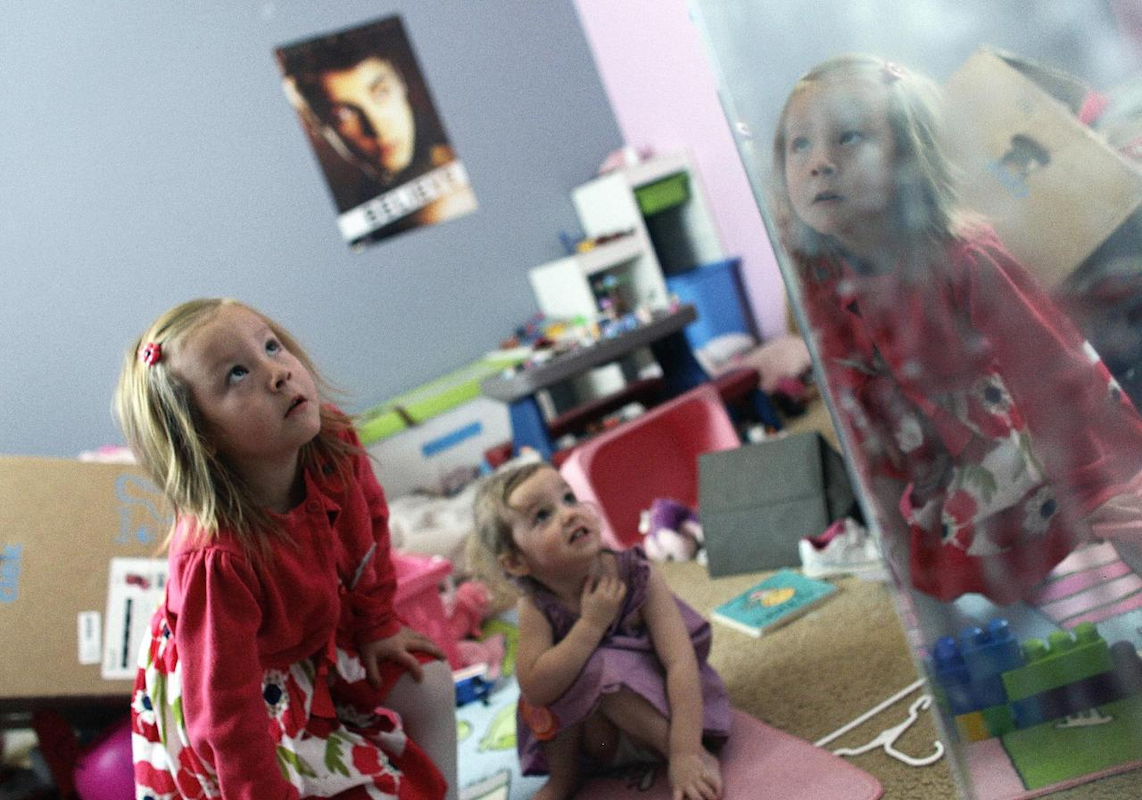 Coy Mathis, left, plays with her sister, Auri, 2, center, as Coy's face reflects in the mirror, at their home in Fountain, Colo., Monday Feb. 25, 2013. Coy has been diagnosed with Gender Identity Disorder. Biologically, Coy, 6, is a boy, but to his parents, three sisters and brother, family members and the world, Coy is a transgender girl. Ideas about gender-disorders began to develop in the 1950s, and have been evolving ever since, both within the medical community, and in American society. (AP Photo/Brennan Linsley)