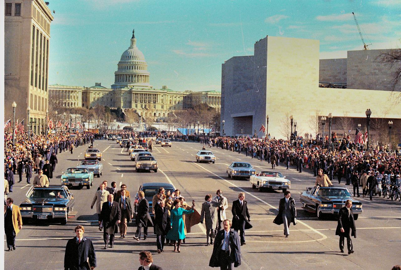 U.S. President Jimmy Carter, center left, and first lady Rosalynn Carter hold hands as they walk down Pennsylvania Avenue during the inaugural parade in Washington, D.C., Jan. 20, 1977.  Carter was sworn in as the nation's 39th president during the inauguration ceremonies earlier.  In the background is the U.S. Capitol building.  (AP Photo)