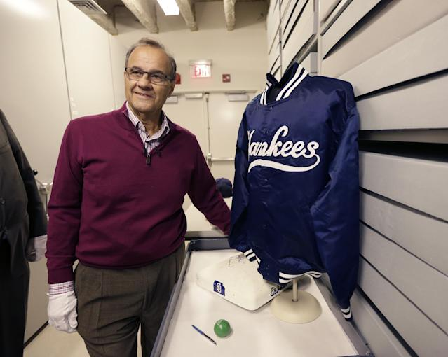 Former New York Yankees manager Joe Torre poses with his jacket from the 1999 World Series during his orientation visit at the Baseball Hall of Fame on Tuesday, March 25, 2014, in Cooperstown, N.Y. Torre will be inducted to the hall in July. (AP Photo/Mike Groll)
