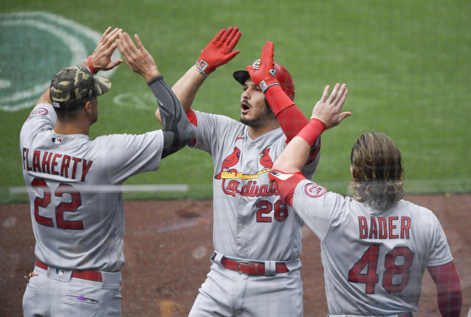 St. Louis Cardinals' Nolan Arenado (28) is congratulated by Jack Flaherty (22) and Harrison Bader (48) after hitting a two-run home run during the first inning of a baseball game against the San Diego Padres Sunday, May 16, 2021, in San Diego. (AP Photo/Denis Poroy)