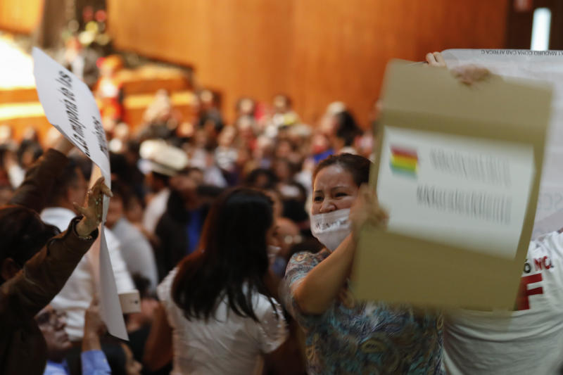 Protesters chant to disrupt a speech by Bolivia's former President Evo Morales, as he speaks with students and members of indigenous communities at Ollin Yoliztli Cultural Center in Mexico City, Tuesday, Nov. 26, 2019. Bolivia is struggling to stabilize after weeks of anti-government protests and violence in which at least 30 people have been killed. Former president Evo Morales resigned on Nov. 10 after an election that the opposition said was rigged. (AP Photo/Rebecca Blackwell)