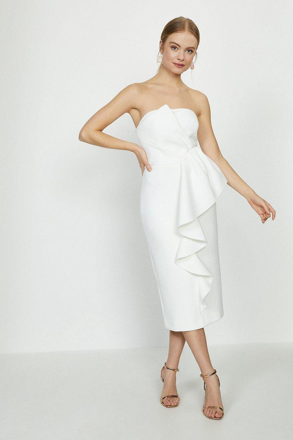 """<p><a class=""""link rapid-noclick-resp"""" href=""""https://go.redirectingat.com?id=127X1599956&url=https%3A%2F%2Fwww.coastfashion.com%2Fruffle-front-bandeau-bridal-dress%2FACC95821.html%3Fcolor%3D133&sref=https%3A%2F%2Fwww.prima.co.uk%2Ffashion-and-beauty%2Ffashion-tips%2Fg34510%2Fwedding-dresses-under-500-pounds%2F"""" rel=""""nofollow noopener"""" target=""""_blank"""" data-ylk=""""slk:SHOP NOW"""">SHOP NOW</a></p><p><br>This midi-style wedding dress is especially elegant with its cascading ruffle front, pencil-shaped skirt and strapless neckline.</p><p>Ruffle Front Bandeau Bridal Dress, £74.25, <a href=""""https://www.coastfashion.com/ruffle-front-bandeau-bridal-dress/ACC95821.html?color=133"""" rel=""""nofollow noopener"""" target=""""_blank"""" data-ylk=""""slk:Coast"""" class=""""link rapid-noclick-resp"""">Coast</a> </p>"""