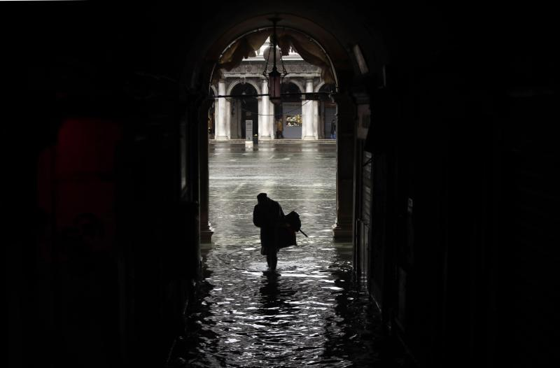 A woman is silhouetted as she walks towards a flooded St. Mark's Square, on the occasion of a high tide, in Venice, Italy, Tuesday, Nov. 12, 2019. The high tide reached a peak of 127cm (4.1ft) at 10:35am while an even higher level of 140cm(4.6ft) was predicted for later Tuesday evening. (AP Photo/Luca Bruno)