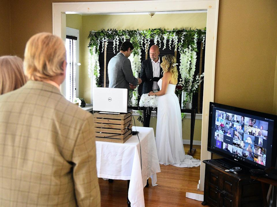 Bride and groom exchange vows with guests watching over Zoom