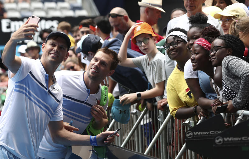 Bob, left, and Mike Bryan of the U.S. pose for a selfie with fans following their third round doubles loss to Croatia's Ivan Dodig and Slovakia's Filip Polasekd at the Australian Open tennis championship in Melbourne, Australia, Monday, Jan. 27, 2020. (AP Photo/Dita Alangkara)