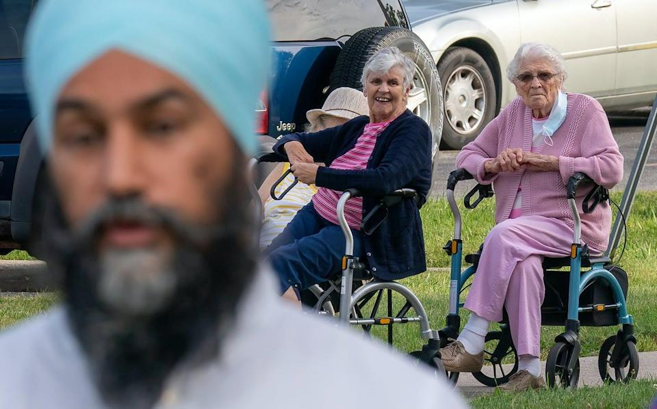 """<span class=""""caption"""">Women look on as NDP leader Jagmeet Singh arrives for a morning campaign announcement in Essex, Ont.</span> <span class=""""attribution""""><span class=""""source"""">THE CANADIAN PRESS/Jonathan Hayward </span></span>"""