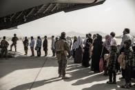 In this image provided by the U.S. Marine Corps, evacuees wait to board a Boeing C-17 Globemaster III during an evacuation at Hamid Karzai International Airport in Kabul, Afghanistan, Monday, Aug. 30. 2021. (Staff Sgt. Victor Mancilla/U.S. Marine Corps via AP)