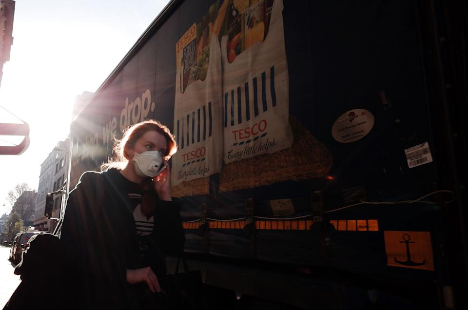 A woman wearing a mask walks past a delivery lorry for supermarket chain Tesco on Jermyn Street in London, England, on March 23, 2020. Across the UK a total of 335 patients who tested positive for the covid-19 coronavirus have now died, with the total number of positive tests this morning standing at 6,650. (Photo by David Cliff/NurPhoto via Getty Images)