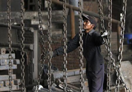 A worker unloads steel bars from a trolley at an iron and steel factory on the outskirts of Jammu