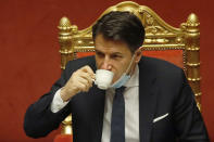 FILE - In this Tuesday, Jan. 19, 2021 file photo, Italian premier Giuseppe Conte sips a coffee during a debate at the Senate prior to a confidence vote, in Rome. When Giuseppe Conte exited the premier's office, palace employees warmly applauded in him appreciation. But that's hardly likely to be Conte's last hurrah in politics. Just a few hours after the handover-ceremony to transfer power to Mario Draghi, the former European Central Bank chief now tasked with leading Italy in the pandemic, Conte dashed off a thank-you note to citizens that sounded more like an ''arrivederci″ (see you again) then a retreat from the political world he was unexpectedly propelled into in 2018. (AP Photo/Alessandra Tarantino, Pool)