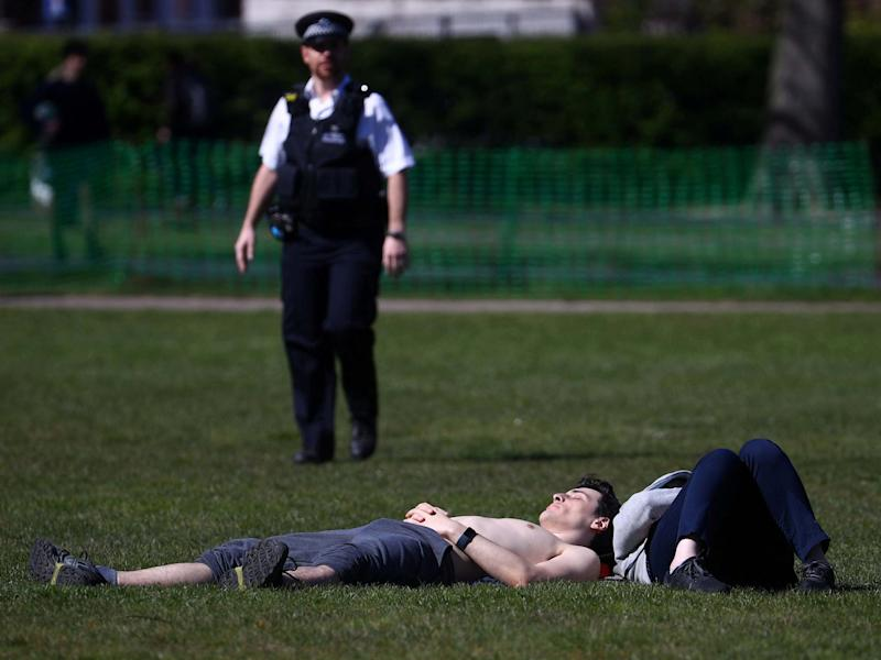 A police officer approaches a sunbather in Greenwich Park, south London: REUTERS