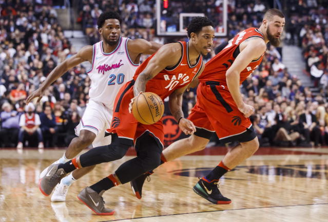 Toronto Raptors DeMar DeRozan goes to the basket with teammate Jonas Valanciunas, right, against Miami Heat Justise Winslow, left, during the first half of an NBA basketball game, Tuesday, Feb. 13, 2018, in Toronto. (Mark Blinch/The Canadian Press via AP)