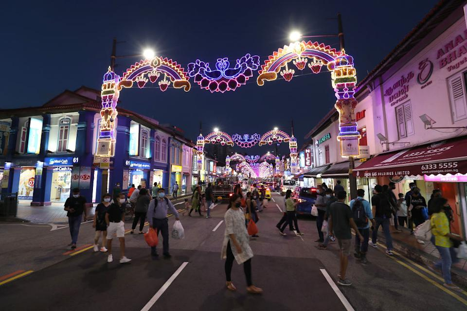 People wearing facemasks as a precaution against the spread of covid-19 cross a street decorated with festival lights ahead of Deepavali in Little India district.