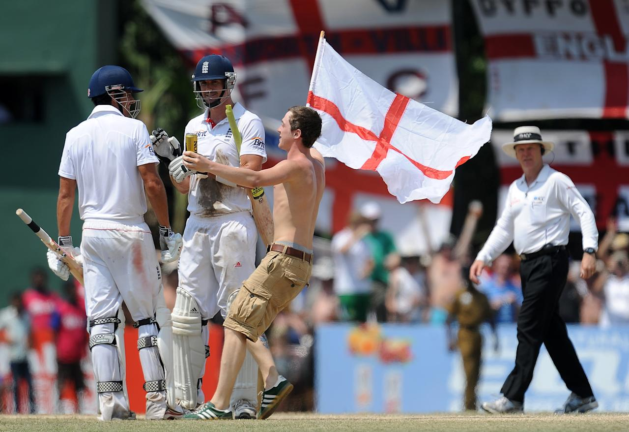 England cricketers Kevin Pietersen (C) and Alastair Cook (L) are congratulated by a cricket fan as they celebrate victory during the final day of the second and final Test match between Sri Lanka and England at the P. Sara Oval crickrt Stadium in Colombo on April 7, 2012.  England defeated Sri Lanka by eight wickets in the second and final Test to level the series 1-1 and retain their number one Test ranking.  AFP PHOTO/ LAKRUWAN WANNIARACHCHI (Photo credit should read LAKRUWAN WANNIARACHCHI/AFP/Getty Images)