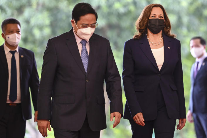 U.S. Vice President Kamala Harris, third from left, walks with Vietnamese Prime Minister Pham Minh Chinh at the government office in Hanoi, Vietnam, Wednesday, Aug. 25, 2021. Harris turns her focus to the coronavirus pandemic and global health during her visit to Vietnam, a country grappling with a worsening surge in the virus and stubbornly low vaccination rates. (Manan Vatsyayana/Pool Photo via AP)