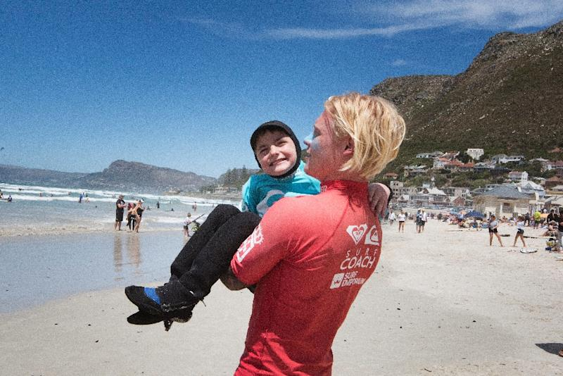A coach carried nine-year-old JJ Booysens to the beach at a recent adaptive surfing event (AFP Photo/RODGER BOSCH)