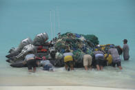 In this April 10, 2021 photo provided by Matthew Chauvin, workers with the Papahanaumokuakea Marine Debris Project push small boats loaded with fishing nets and plastic off Kure Atoll in the Northwestern Hawaiian Islands. A crew has returned from the remote Northwestern Hawaiian Islands with a boatload of marine plastic and abandoned fishing nets that threaten to entangle endangered Hawaiian monk seals and other marine animals on the tiny, uninhabited beaches stretching for more than 1,300 miles north of Honolulu. (Matthew Chauvin, Papahanaumokuakea Marine Debris Project via AP)