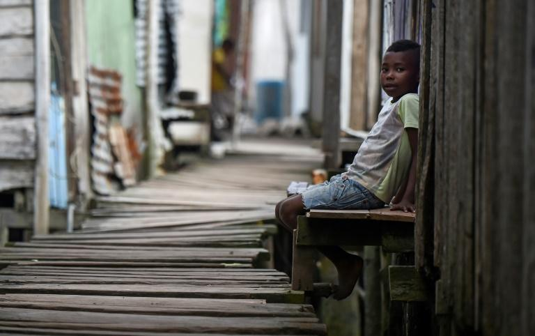 A boy sits on a bench in Ciudad 2000, a shantytown that is home to people displaced by turf wars between criminal gangs in Tumaco described as one of the epicenters of Colombian drug violence