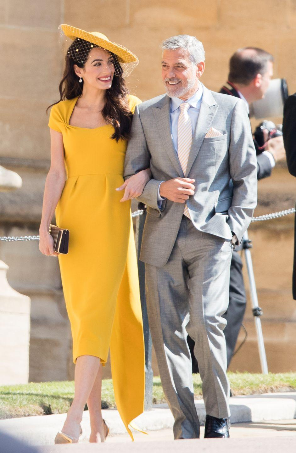 <p>Radiant in sunshine yellow and matching hat, Amal Clooney looked incred walking arm-in-arm with George. She appears so relaxed, you'd have no idea she was attending the royal wedding of Harry and Meghan, streamed live to billions of people. </p>