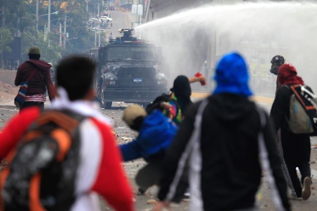 <p>Supporters of Salvador Nasralla, presidential candidate for the Opposition Alliance Against the Dictatorship, throw rocks toward a police water cannon during a protest while awaiting for official presidential election results in Tegucigalpa, Honduras, Nov. 30, 2017. (Photo: Jorge Cabrera/Reuters) </p>