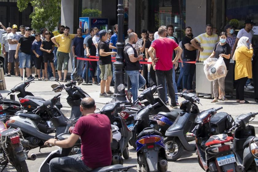 People queue for bread outside a bakery in Beirut, Lebanon, Saturday, June 27, 2020. (AP Photo/Hassan Ammar)
